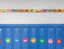 蓝色衣物柜和五颜六色的横幅欢迎学生回到学校 库存照片