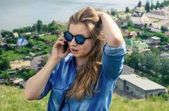 蓝色衣裳的女孩谈话在电话 库存照片