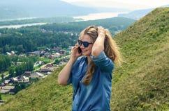 蓝色衣裳的女孩谈话在电话 免版税库存照片