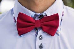 蓝色衬衣和红色弓领带的人 免版税图库摄影