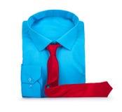蓝色衬衣和红色领带在白色背景 免版税库存照片