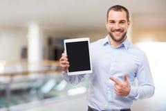 蓝色衬衣展示屏幕的人在商业中心 免版税库存照片