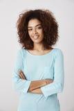蓝色衬衣微笑的摆在的非洲女孩与横渡的胳膊 免版税库存照片