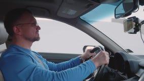 蓝色衬衣推进汽车和watchis录影的白人在智能手机 影视素材