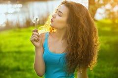 蓝色衬衣的可爱,年轻,卷曲女孩,拿着微笑的蒲公英开花和 免版税库存照片