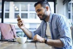 蓝色衬衣的商人使用释放无线的连接4G咖啡馆的互联网 库存照片