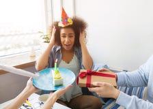 蓝色衬衣的女孩今天有一个生日 她的朋友做了她的某一惊奇 他们举行礼物和a 图库摄影