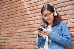 蓝色衬衣的妇女听到与耳机的音乐的 免版税库存图片