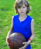 蓝色衬衣的男孩有篮球的 免版税库存照片