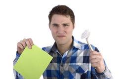 蓝色衬衣的年轻人有清洁器物的没有发笑 免版税库存照片