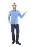 蓝色衬衣的年轻阿拉伯商人指向某事的是 库存照片