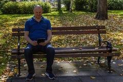 蓝色衬衣读书的人与在公园长椅的数字式片剂 免版税库存图片