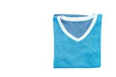 蓝色衬衣 在白色的被折叠的T恤杉 免版税库存照片