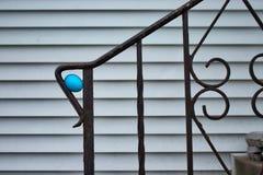 蓝色被洗染的复活节彩蛋,掩藏为蛋狩猎,在篱芭栏杆弯曲处在中西部的家具体台阶的  免版税库存图片