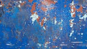 蓝色被绘的金属背景,与许多镇压,剥的和剥落的油漆 生锈的纹理 免版税库存图片