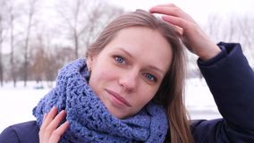 蓝色被编织的围巾的俏丽的蓝眼睛的妇女在看照相机的冬天城市公园和长期改正她 影视素材