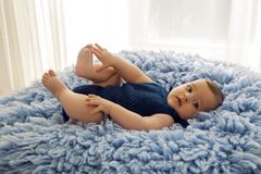 蓝色被编织的连衫裤衣裳的婴孩 免版税库存照片