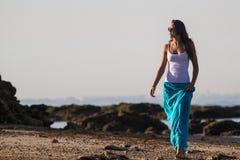 蓝色裙子的女孩在海滩 免版税库存图片