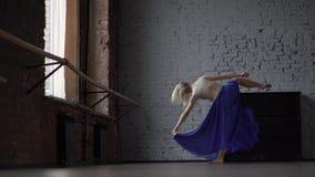 蓝色裙子的白肤金发的舞蹈家在慢动作的一条腿做分裂 股票录像