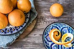 蓝色西班牙手工制造板材用桔子,在木桌上的果皮 免版税库存照片