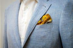 蓝色西装有一件白色衬衣的和有在口袋的一条黄色围巾的 免版税库存照片