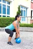 蓝色训练的运动的西班牙妇女与做死的推力的kettlebell 免版税库存照片