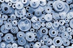 蓝色设色了塑料齿轮和钝齿轮在黑背景 免版税库存图片