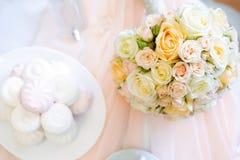 蓝色详细资料花袜带系带婚礼 新娘轻的玫瑰` s花束顶视图在与香水和arshmallow甜点的桌上开花 平的位置 S 免版税图库摄影