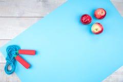 蓝色跳绳用在一张蓝色席子的苹果 库存图片