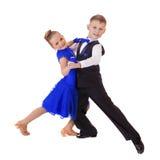 蓝色跳舞礼服的愉快的小女孩 免版税库存照片