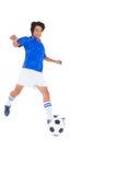 蓝色踢的球的足球运动员 库存照片