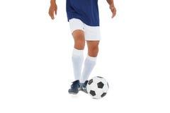 蓝色踢的球的足球运动员 免版税库存照片