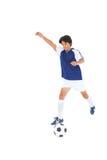 蓝色踢的球的足球运动员 库存图片