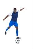 蓝色踢的球的足球运动员 免版税库存图片