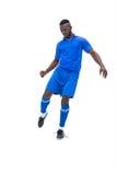 蓝色踢的足球运动员 库存图片