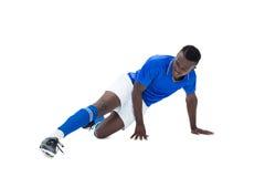 蓝色踢的足球运动员 图库摄影