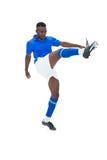 蓝色踢的足球运动员 库存照片
