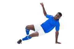 蓝色踢的足球运动员 免版税图库摄影