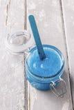 蓝色身体在木桌上洗刷 库存图片