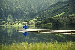 蓝色运动衫的年轻人在码头站立在火山的湖旁边 库存照片