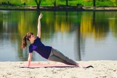 蓝色运动衫的浅黑肤色的男人在做在海滩的健身席子锻炼 做健身锻炼的妇女户外 库存图片