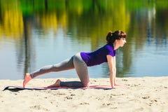 蓝色运动衫的浅黑肤色的男人在做在海滩的健身席子锻炼 做健身锻炼的妇女户外 图库摄影