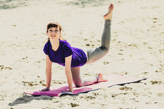 蓝色运动衫的浅黑肤色的男人在做在海滩的健身席子锻炼 做健身锻炼的妇女户外 免版税库存图片