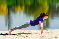蓝色运动衫的浅黑肤色的男人在做在海滩的健身席子锻炼 做健身锻炼的妇女户外 库存照片