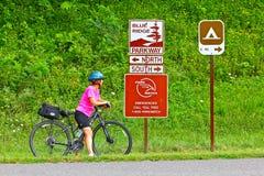 蓝色里奇大路的女性自行车骑士 免版税库存照片