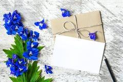 蓝色野花和空白的白色贺卡花束与信封 图库摄影