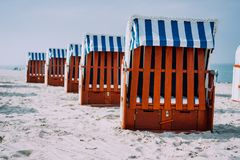 蓝色镶边被顶房顶的木椅子在沙滩站在队中在晴天 特拉沃明德, Luebeck,德国 图库摄影