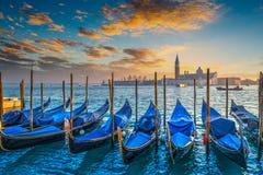 蓝色长平底船在日落的威尼斯 库存图片