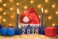 蓝色闪亮金属片、一个球、蜡烛、一个盖帽和一件礼物与数值2018年在桌在一本新年` s诗歌选的背景有gol的 免版税库存照片