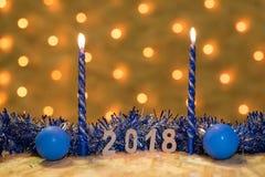 蓝色闪亮金属片、球和蜡烛与数值2018年在桌在一本新年` s诗歌选的背景有金黄光的 免版税库存图片